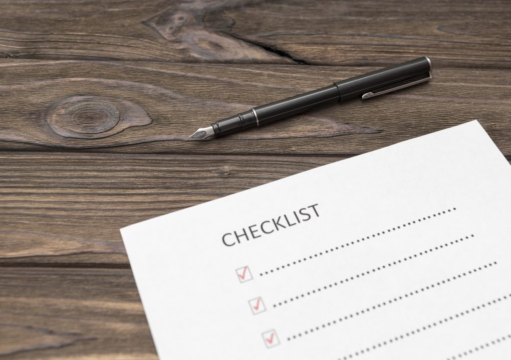 a checklist on a sheet of paper, a pen on a wooden table